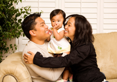 parents holding baby girl on couch and smiling