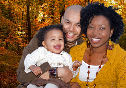 African-American couple holding their baby and smiling